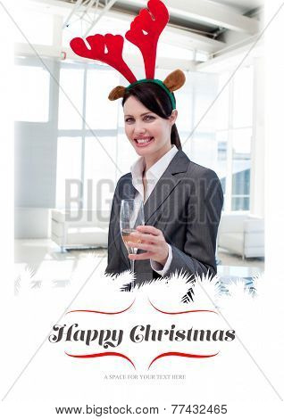 Smiling businesswoman with a novelty Christmas hat toasting with Champagne against border