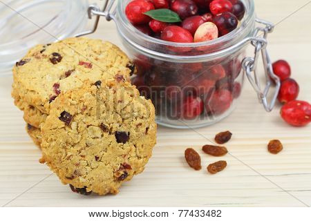 Crunchy cookies with cranberries leaning against jar of fresh cranberries