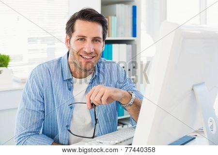 Editor working at his computer while looking at camera in office