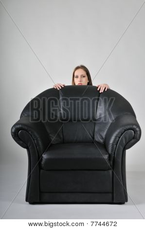 Young Woman Hiding Behind Big Armchair