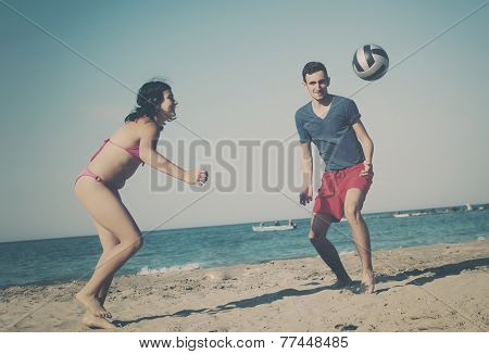 Couple Playing Volleyball On The Beach