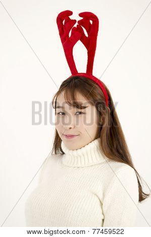 Young beautiful asian woman wearing Christmas antlers