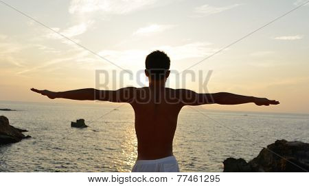 asian man acts yoga on the beach in the morning