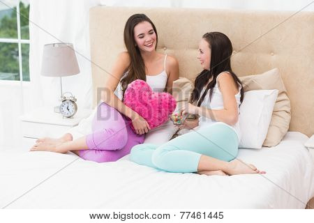Pretty friends chatting on bed at home in the bedroom