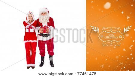Santa and Mrs Claus smiling at camera offering gift against orange vignette