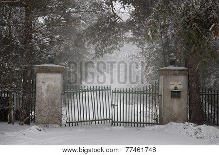 Spooky old broken gate on driveway in winter