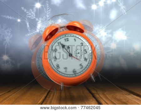 Alarm clock counting down to twelve against shimmering light design over boards