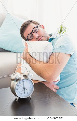 Bored man beside alarm clock hugging a pillow at home in the living room