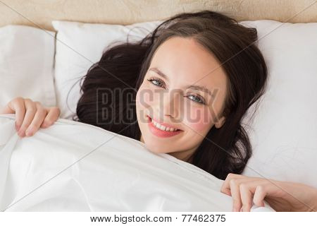 Pretty brunette under the duvet at home in the bedroom