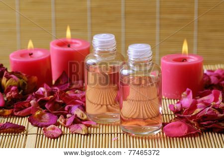 Set of rose petals with row of candle  with massage oil on mat