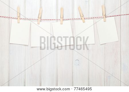 Photo frames hanging on rope over white wooden background