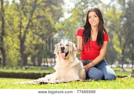 Girl sitting in park with her pet dog