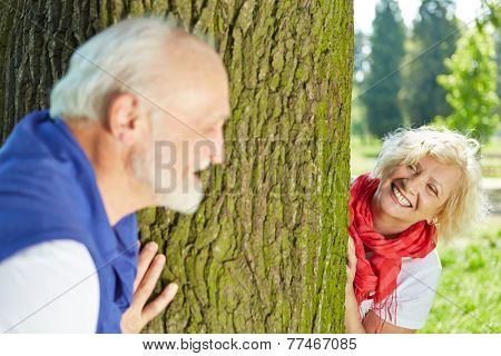 Happy senior couple playing hide and seek together in nature