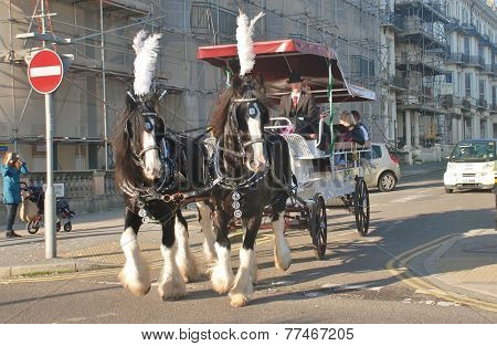 ST.LEONARDS-ON-SEA, ENGLAND - NOVEMBER 29, 2014: Horses pull a carriage giving rides around Warrior Square at the St.Leonards Frost Fair. The event promotes local trade in the approach to Christmas.