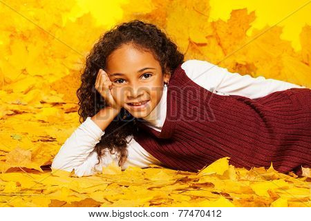 Little black girl lays on the autumn maple leaves