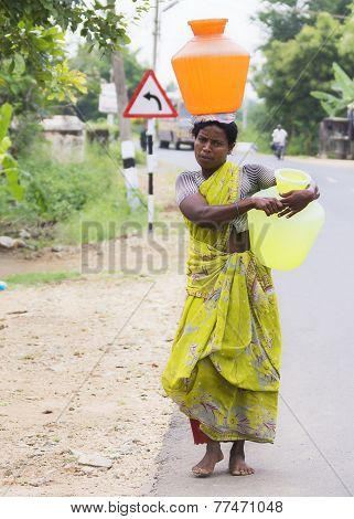 Woman Carries Two Jugs Of Water.