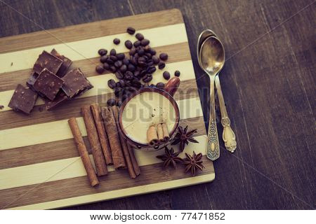 Cup of hot coffe with cinnamon sticks on vintage wooden background, selective focus