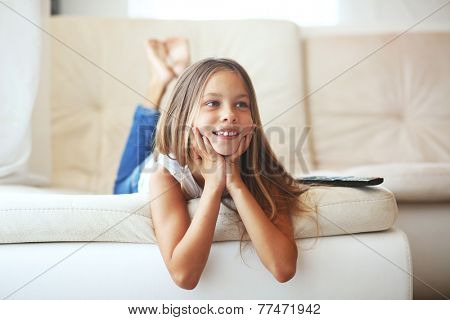 8 years old child watching tv laying down on a sofa at home alone