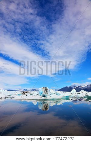 Glacial Lagoon in Iceland. Cirrus clouds and spectacular icebergs are reflected in the ocean lagoon