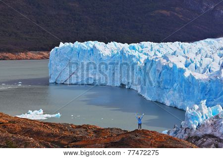 The woman - tourist admire the white-blue icy splendor. Giant lake Perito Moreno glacier