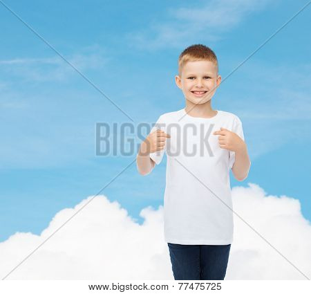advertising, gesture, people and childhood concept - smiling little boy in white t-shirt pointing fingers at himself over sky background
