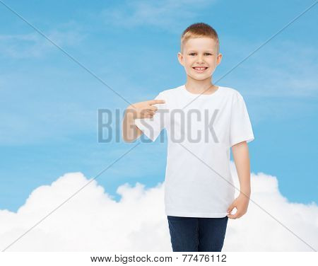 advertising, gesture, people and childhood concept - smiling little boy in white t-shirt pointing finger at himself over sky background