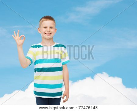 childhood, gesture and people concept - smiling little boy in casual clothes making ok gesture over blue sky background