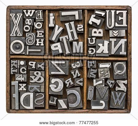 alphabet and other symbols in old metal type printing blocks in a rustic wooden typesetter box