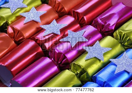 Row Of Shiny Festive Christmas Cracker Bon Bons In Bright Cheerful Red, Pink, Orange, Blue And Green