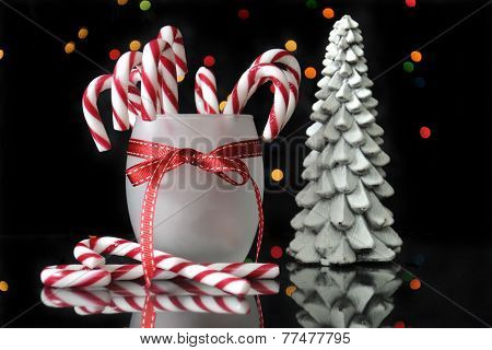 Festive Christmas Candy Canes And Trees On Reflective Table With Bokeh Lights On Black Background.