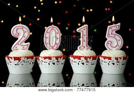 Happy New Year For 2015 Red Velvet Cupcakes In Red And White Theme With Lit Candles On Reflective Ta