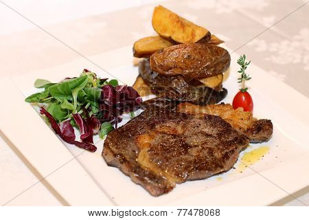 Pork steak with potatoes on white plate