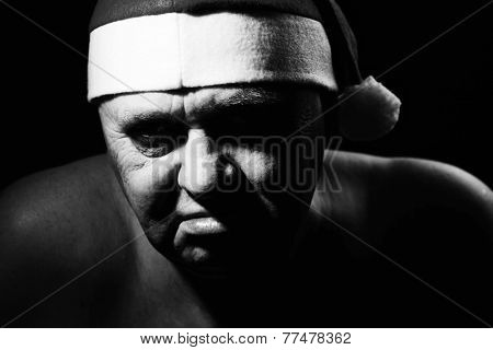 Close up black and white portrait of ominous mature man in Santa Claus hat