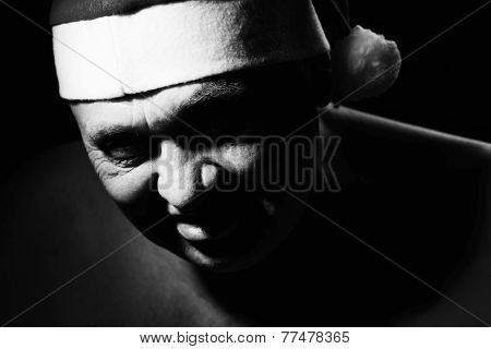 Close up black and white portrait of gloomy and scary mature man in Santa Claus hat