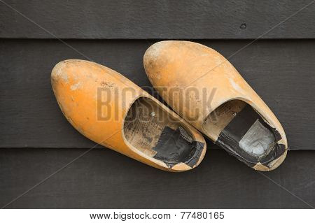 Dutch Clogs On The Wooden Wall.