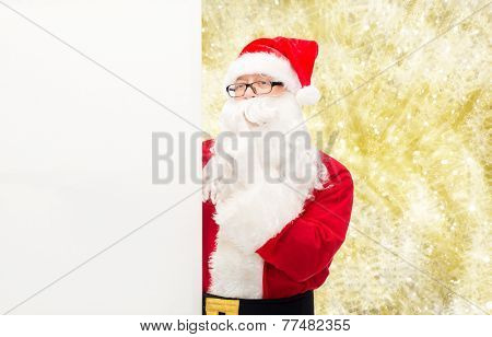 christmas, holidays, advertisement and people concept - man in costume of santa claus with white blank billboard making hush gesture over yellow lights background