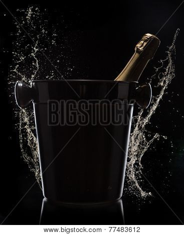 Champagne bucket on black background, celebration theme.