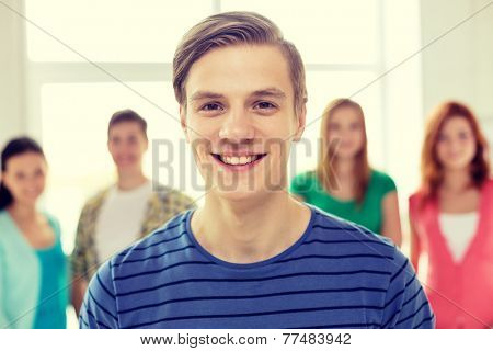 education and school concept - group of smiling students with teenage boy in front