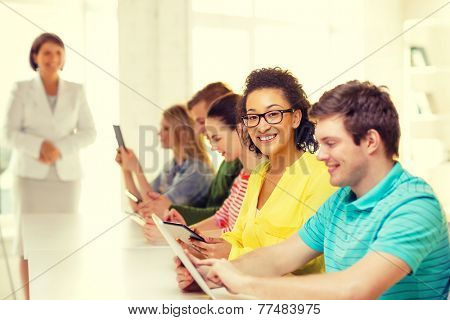 education, technology and internet concept - smiling female students with tablet pc computer and friends on the back at school