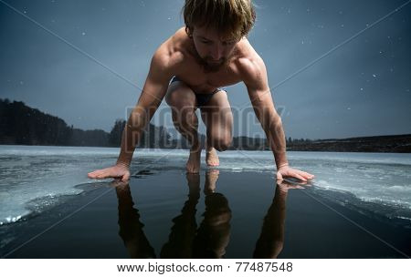 Young man ready to immerse into ice hole on the winter pond