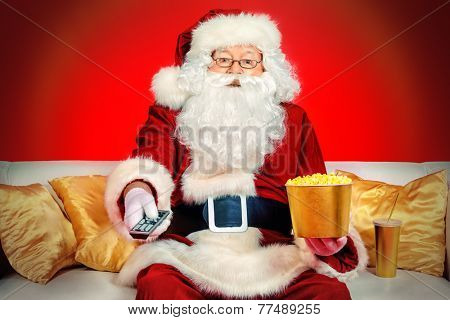 Traditional Santa Claus sitting on the couch watching TV, eating popcorn and drinking soda. Christmas. Red background.