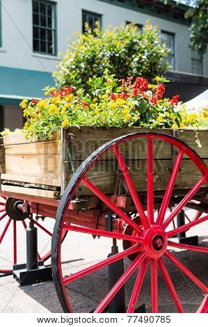 Flowers In Wagon Over Red Wheel