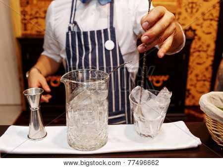 Bartender is making cocktail at the bar counter