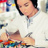 pic of microprocessor  - girl student studying electronic device with a microprocessor - JPG