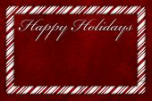 stock photo of candy cane border  - A Happy Holidays card A Candy Cane border with words Happy Holidays over red plush background with copy - JPG