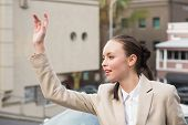 stock photo of hail  - Young businesswoman hailing a cab outside in the city - JPG