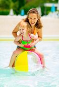 foto of pool ball  - Portrait of happy mother and baby girl playing with beach ball in pool - JPG