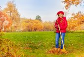 stock photo of beret  - Beautiful small girl with rake cleaning grass from fallen leaves in the autumn park during daytime wearing red coat and beret - JPG