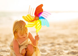 stock photo of windmills  - Baby girl playing with colorful windmill toy on beach - JPG