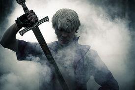 foto of sword  - portrait of a brutal warrior with sword in smoke - JPG